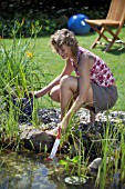 LADY CHECKING POND WATER TEMPERATURE WITH THERMOMETER