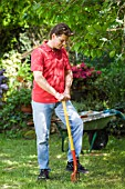 MAN AERATING LAWN WITH FORK