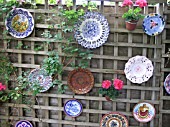 PLATES USED TO DECORATE GARDEN FENCE