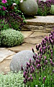 LAVANDULA STOECHAS AGAINST PAVED PATH WITH DECORATIVE STONE BALLS