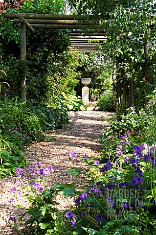 GRAVEL_PATH_COVERED_BY_PERGOLA_LEADING_TO_FORMAL_URN_ON_STAND