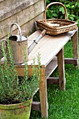 WOODEN BENCH WITH WICKER BASKET AND WATERING CAN.
