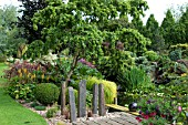 JOHNS GARDEN AT ASHWOOD NURSERIES   POOL WITH SURROUNDING SHRUBS CONIFERS TREE AND STAGING