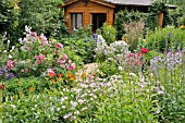 WOODEN HOUSE IN A RICH FLOWERING GARDEN. DESIGN: MARIANNE AND DETLEF LUEDKE