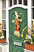 HOUSE ENTRANCE WITH EASTER DECORATION AND SPRING FLOWERS