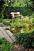 GARDEN BENCH AT A POND WITH A STONE BRIDGE. DESIGN: MARIANNE AND DETLEF LUEDKE