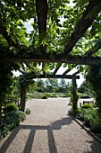 THE ENTRANCE TO THE GARDENS AT RHS GARDEN,  HYDE HALL,  IS THROUGH THIS ARCH OF CLEMATIS AND WISTERIA