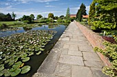THE TOP POND AT RHS GARDEN,  HYDE HALL WITH A PATH AND LOW WALL RUNNING ALONG SIDE THE WATER.