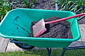 PLASTIC WHEELBARROW WITH COMPOST AND SPADE
