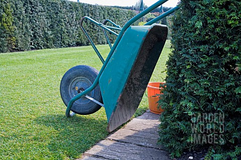 PLASTIC_WHEELBARROW_TIPPED_OVER_AND_RESTING_AGAINST_A_YEW_HEDGE