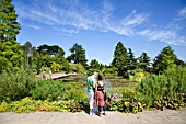 VISITORS WANDER AROUND THE TOP POND AT RHS HYDE HALL GARDENS