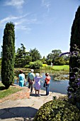 VISITORS WANDER AROUND THE TOP POND AT RHS HYDE HALL GARDENS IN ESSEX.