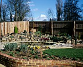 NEW GARDEN IN DEVELOPMENT 1 FEBRUARY WINTER. VIEW ACROSS THE GARDEN TO POND AND ROCKERY.