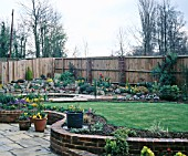 NEW GARDEN IN DEVELOPMENT APRIL,  VIEW ACROSS THE LAWN TO POND AND ROCKERY.