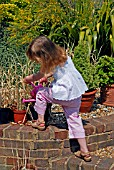 CHILD WATERING PLANT IN POT WITH A WATERING CAN,  SURREY: LATE JUNE