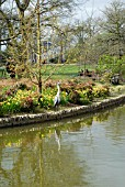 VIEW OF SEVEN ACRES LAKE WITH THE BICENTENARY GLASSHOUSE IN THE BACKGROUND. RHS WISLEY: APRIL