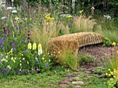 JORDANS WILDLIFE GARDEN DESIGNED BY SELINA BOTHAM. NATURAL PLANTING WITH SCULPTURED STRAW BENCH